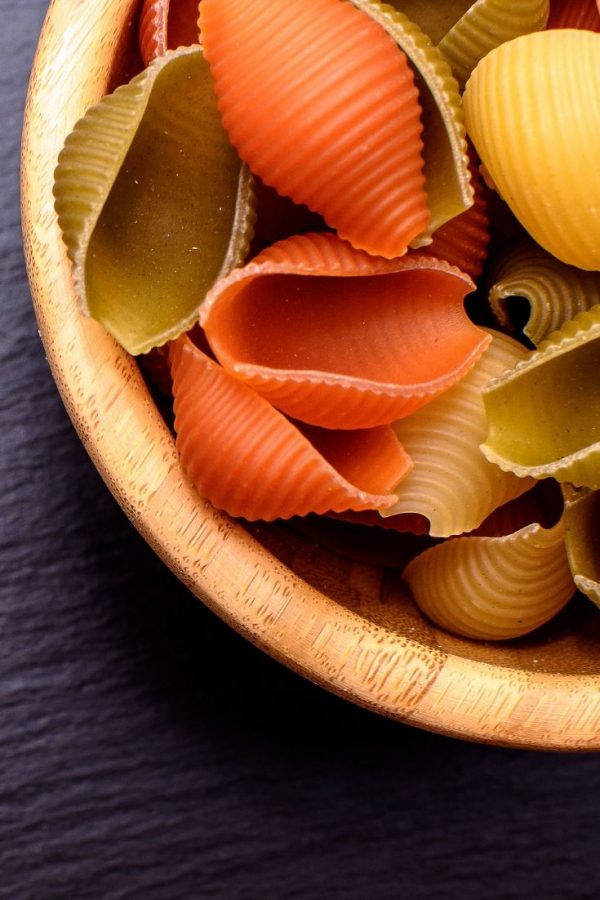 colorful shell pasta in a wodden bowl on a black surface
