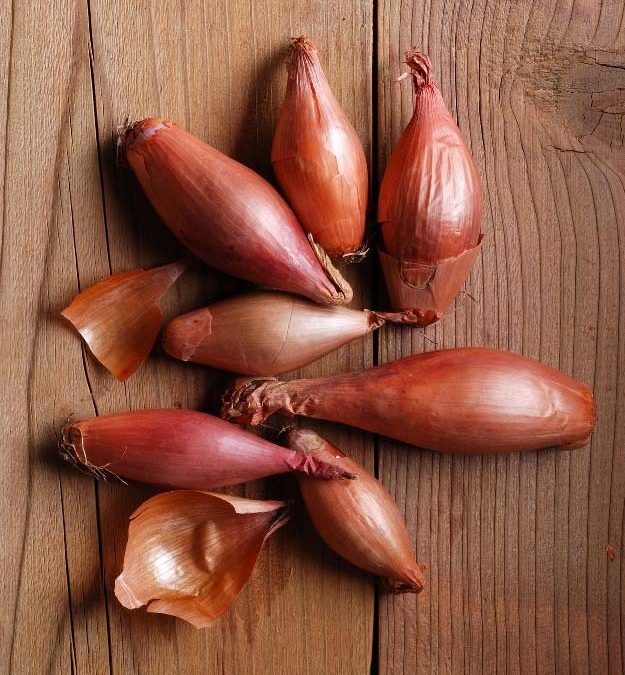 seven shallots lying on a wooden surface