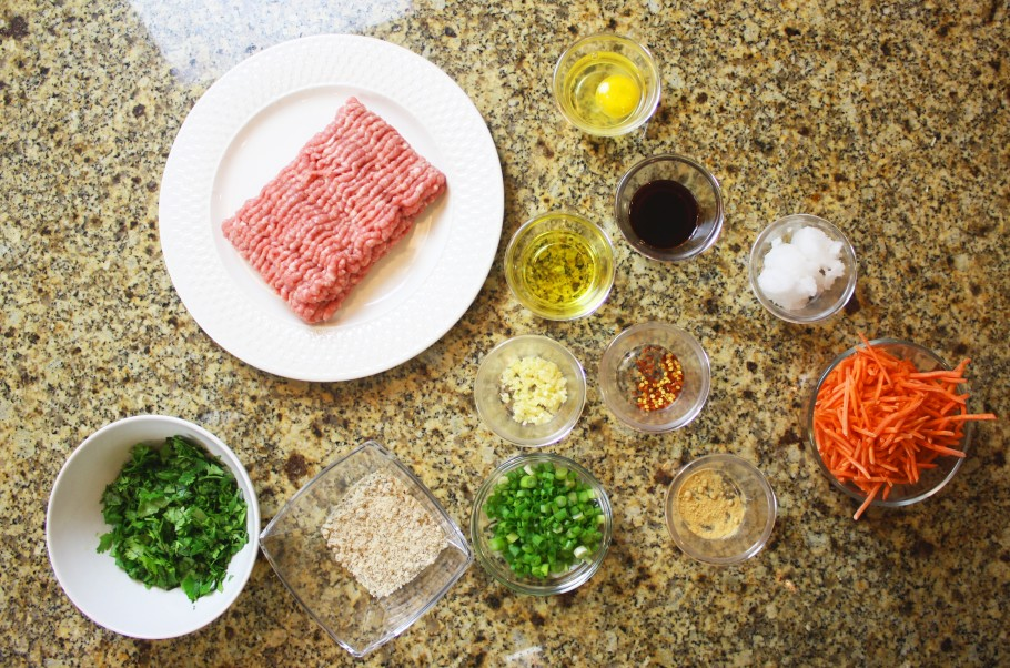 Ingredients for meatballs in separate bowls on granite surface