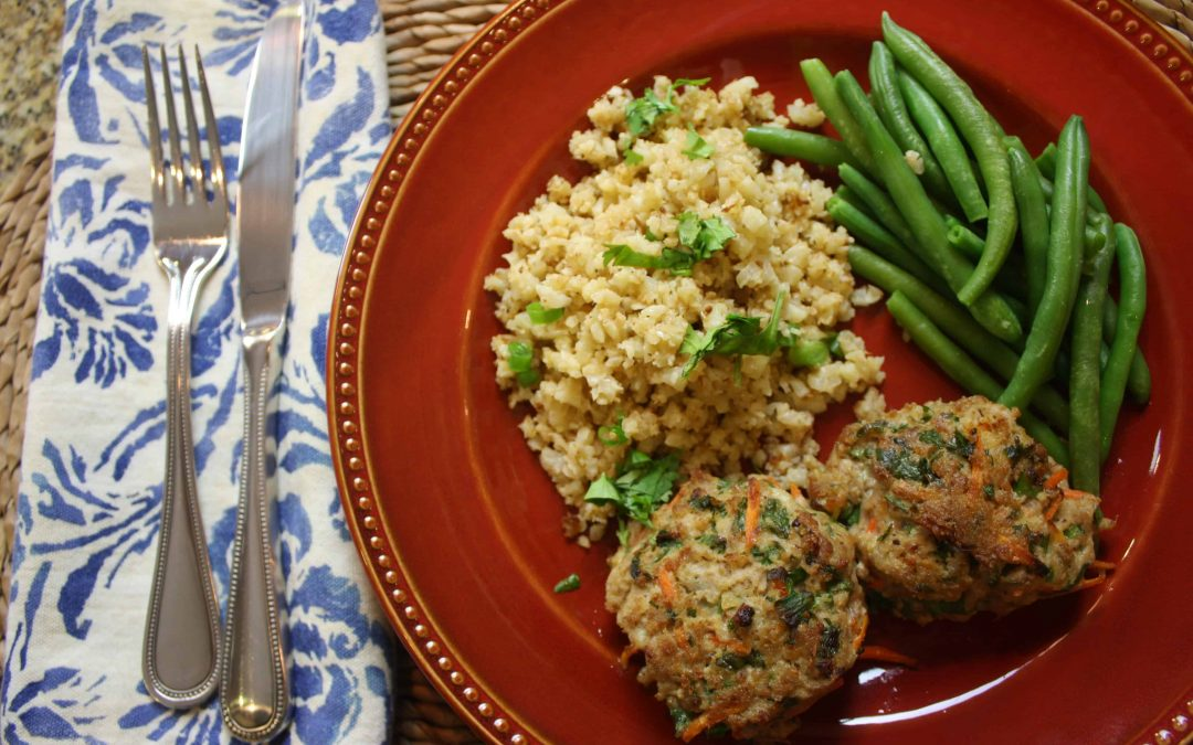 Meatballs served with green beans and cauliflower rice on red plate with utensils