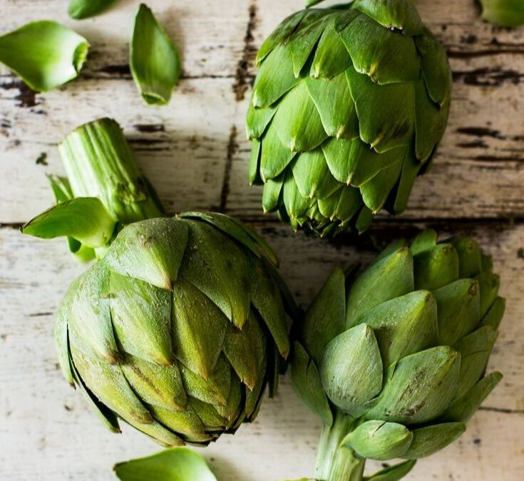Three artichokes and a few loose leaves on a distressed white background