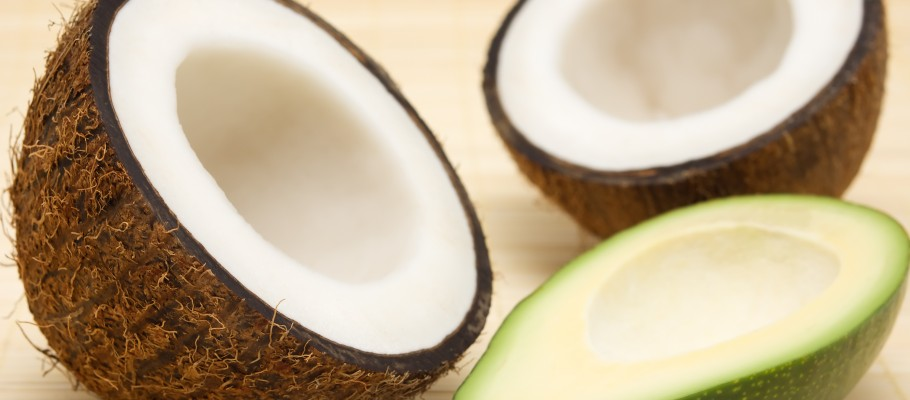 Two halves of coconut, avocado on a rug.