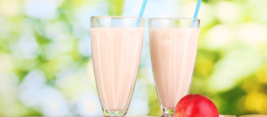 Peach milk shakes on wooden table on bright background