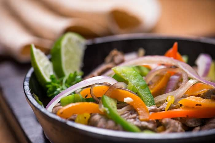 Beef fajita in the pan with tortilla bread.