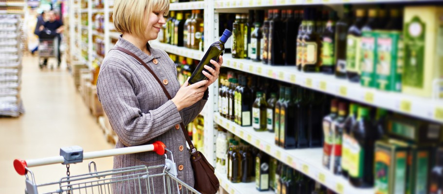 Woman reading the label on a bottle of olive oil in the store