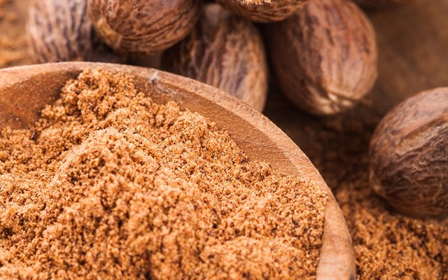 Ground nutmeg spice in the wooden spoon closeup
