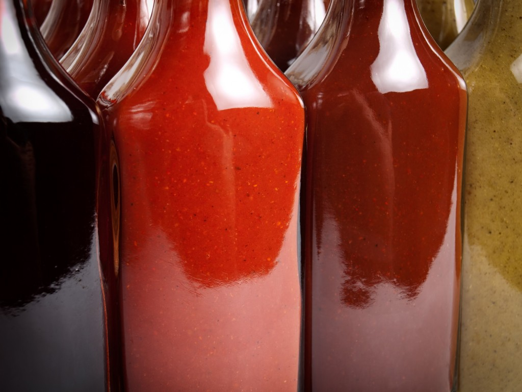 Closeup view of several glass bottles filled with various types of hot sauces.