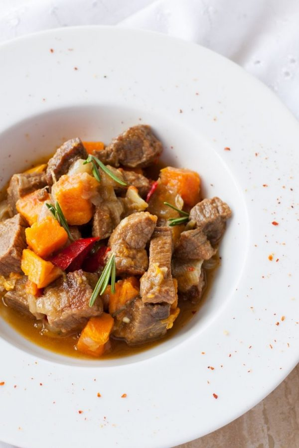 Beef & Butternut Squash Stew in a white bowl with the edge sprinkle with a red spice