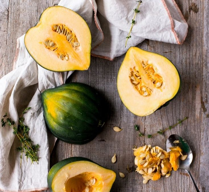 Acorn Squash, some whole, some cut, laying on a wooden surface with a cloth and a spoon for scooping seeds
