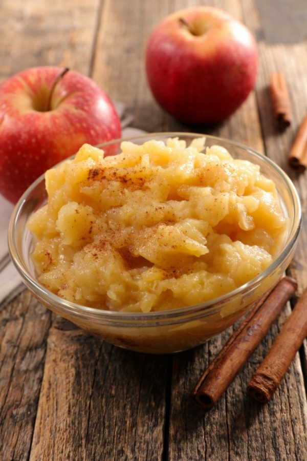Bowl of applesauce on a wooden surface next to whole apples and cinnamon sticks