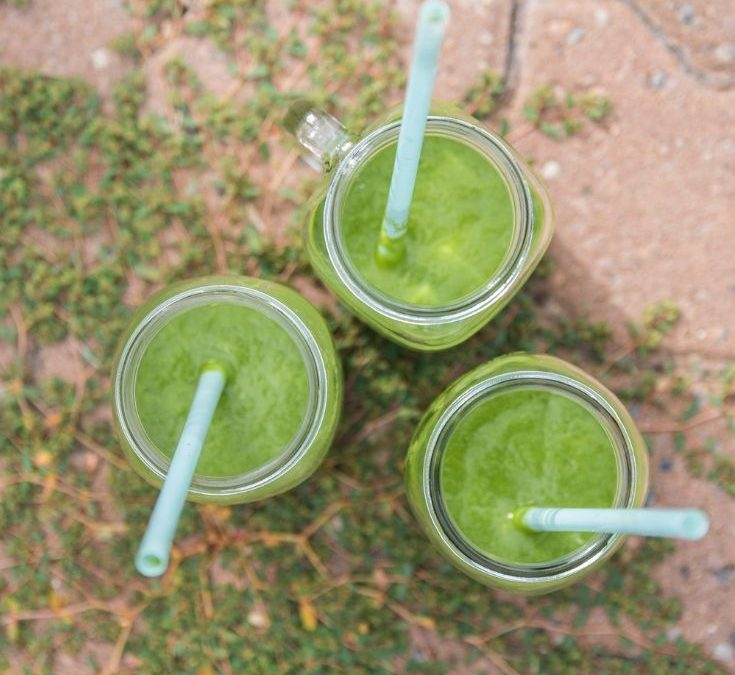Three green smoothies in mason jars, shown from above on ivy covered red tile