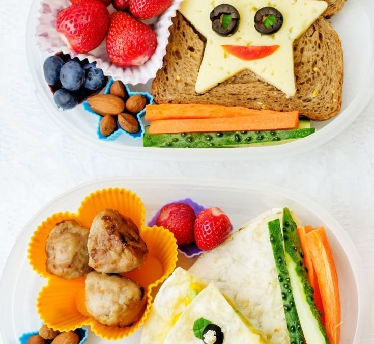 two children's bento box lunches on a white background