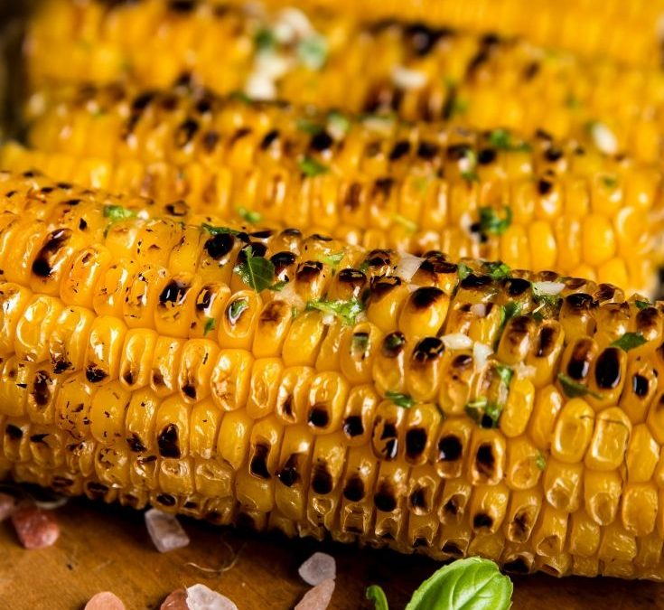 grilled corn on the cob on a wooden cutting board with pink salt scattered