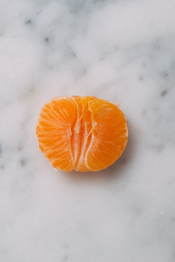 Half of a peeled Mandarin Orange on a white marble surface