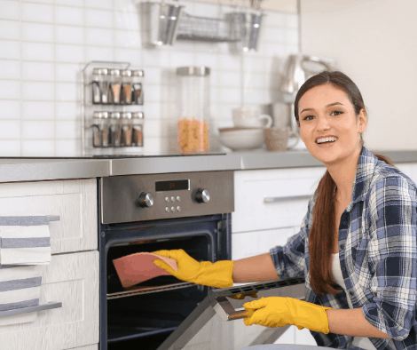 Smiling woman cleaning oven