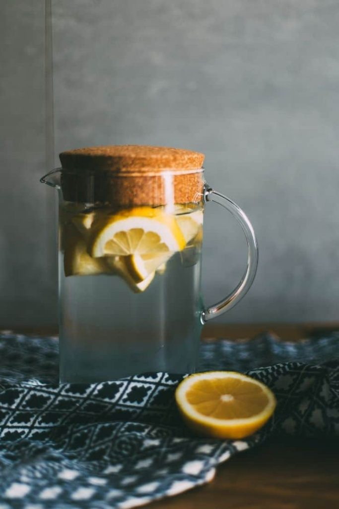 A pitcher filled with water and lemon slices next to half a lemon on top of a plaid dish cloth.