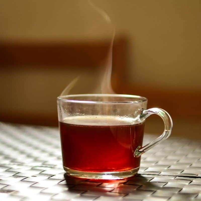 Clear cup of hot tea on a woven mat