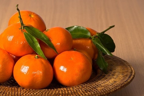 Fresh juicy tangerines fruits in natural woven bowl