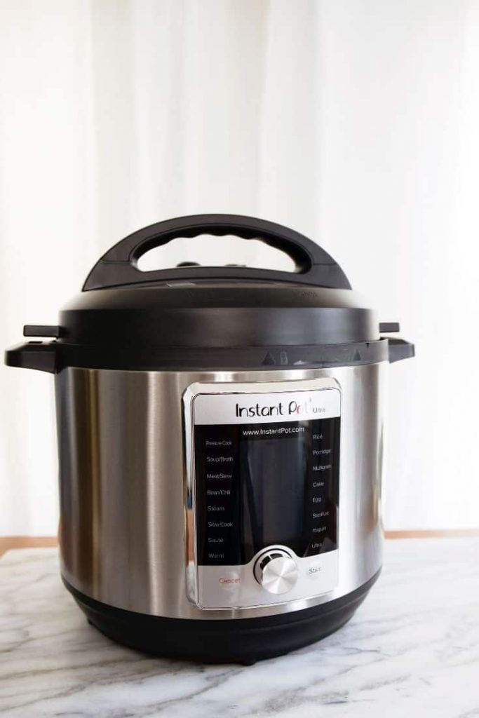 Instant Pot on a light marble surafce with white background