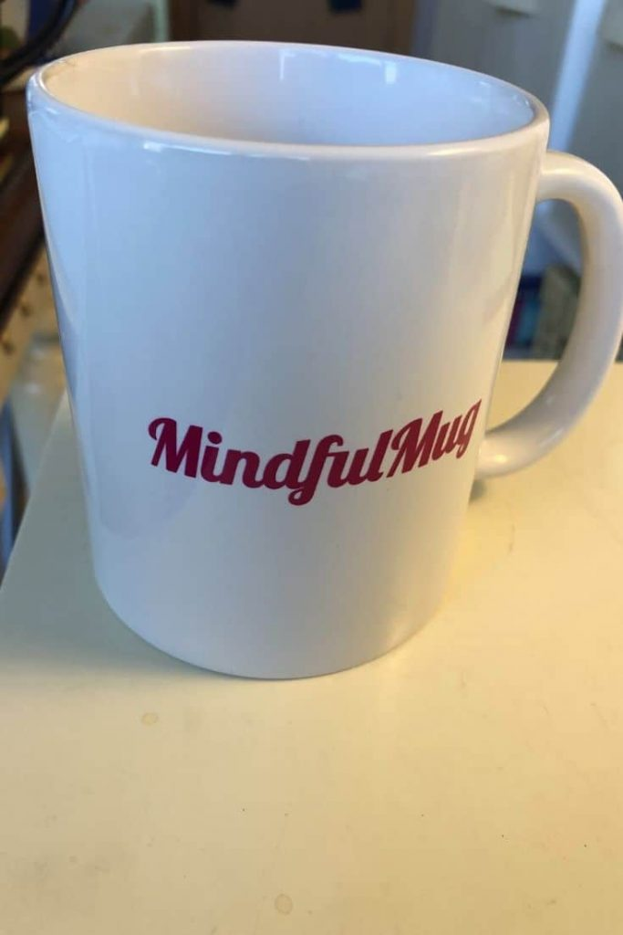 """White mug with """"Mindful Mug"""" in red lettering."""