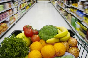 A grocery cart filled with nutritious fruits and vegetables.