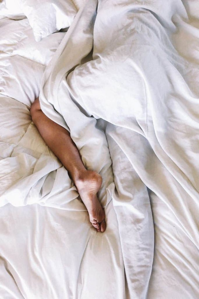 woman lying in white bedding with one leg out from under the covers