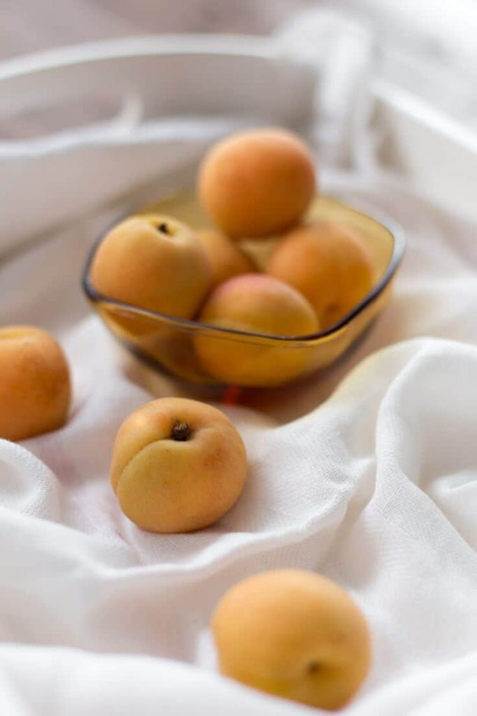 Peaches in a bowl and a few loose on a draped white cloth surface
