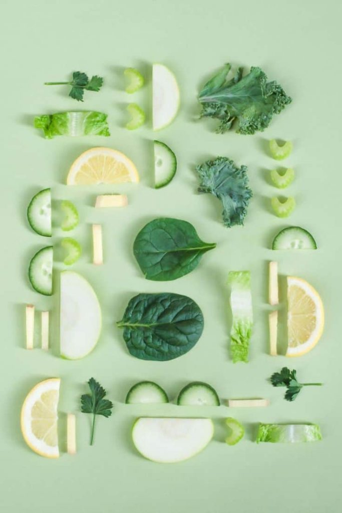 Green vegetables and lemons sliced and laid artistically on a green background