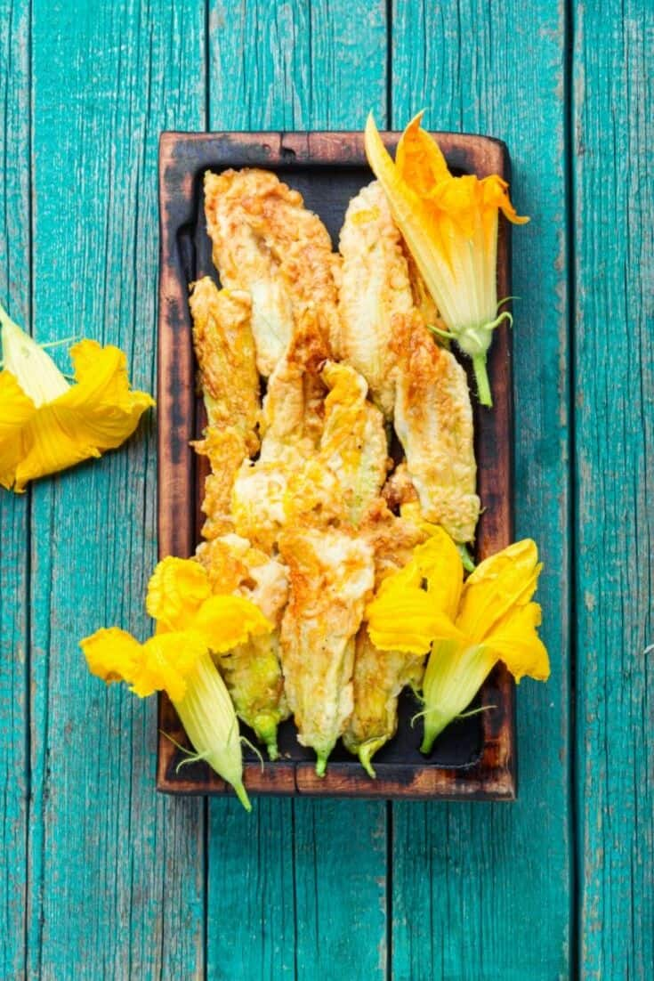 Squash Blossoms on a wooden tray laying on a dark teal wooden table