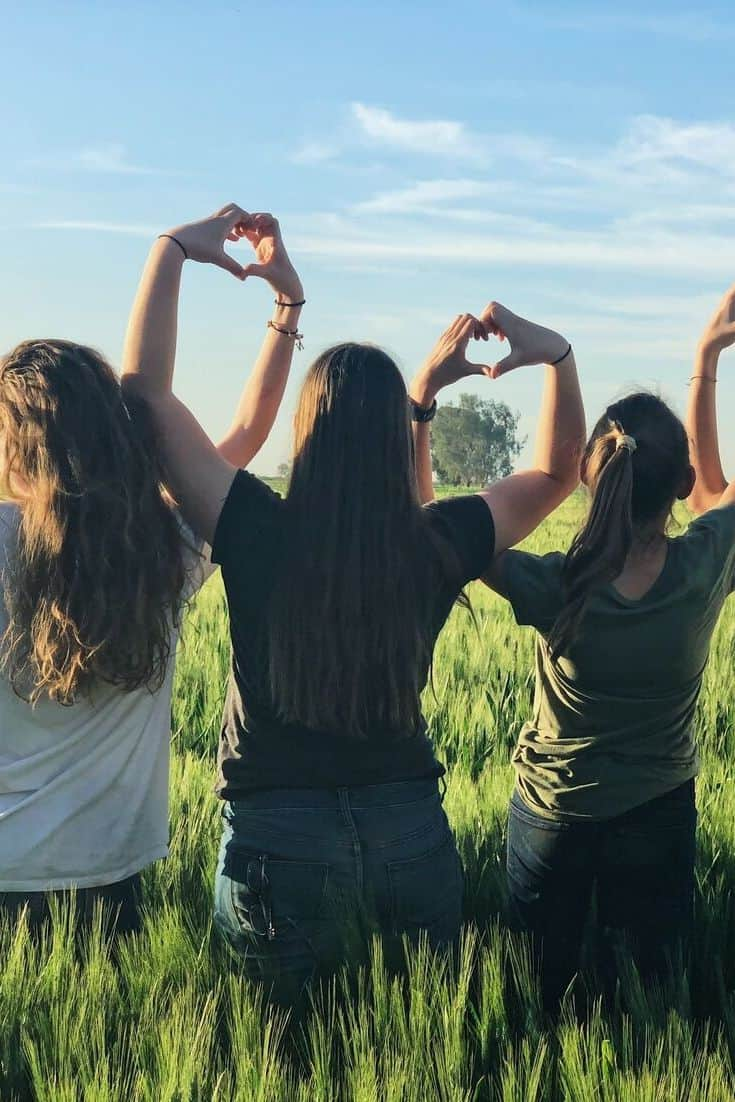 women standing ina field with their backs to the camera crossing arms in the air to make heart gestures.