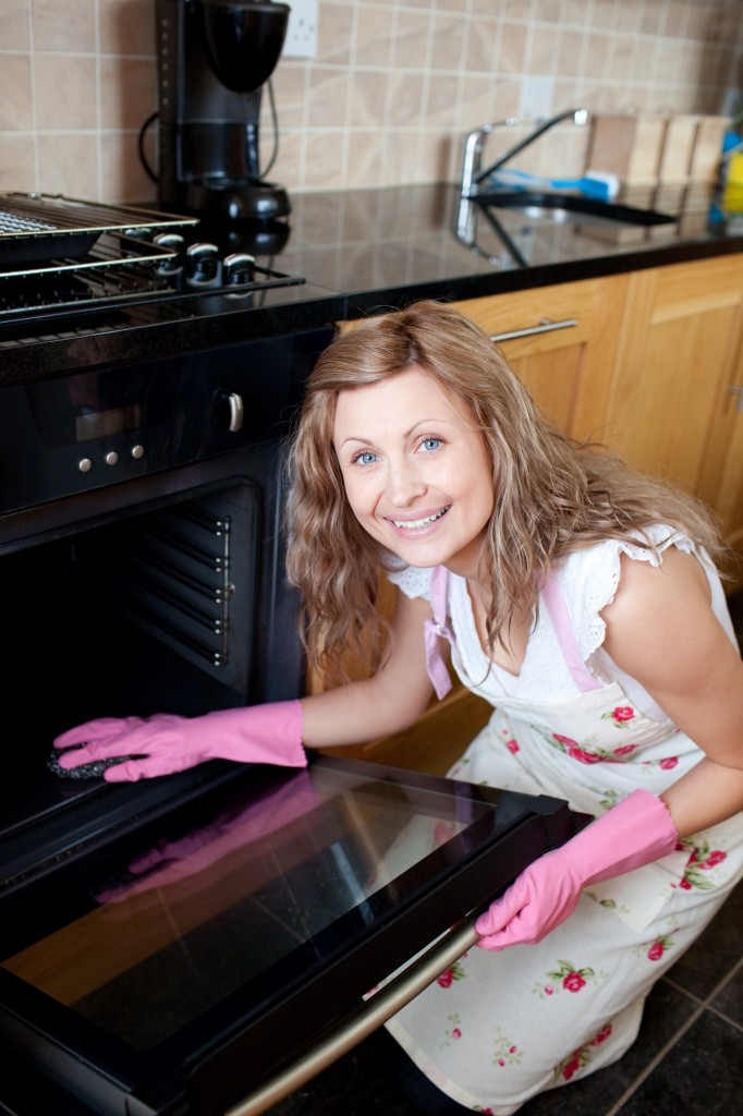 Smiling woman cleaning the oven in the kitchen