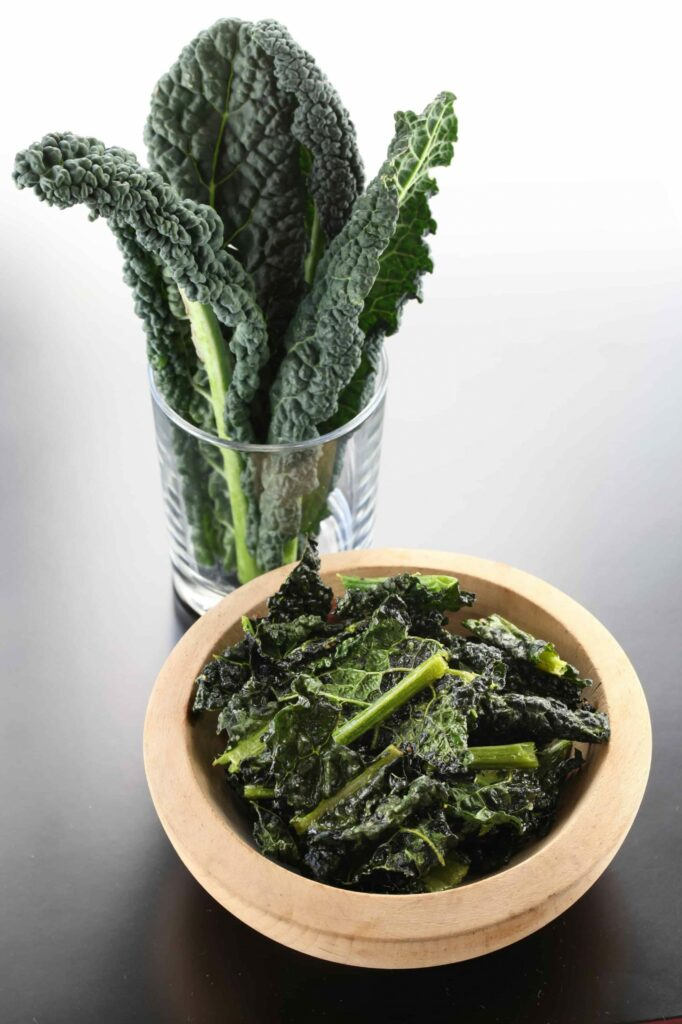 Dino kale standing in a small glass next to a bowl of chopped dino kale