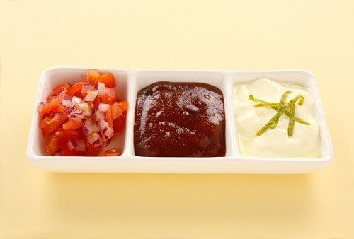 Indian condiments consisting of yoghurt and lime, chutney and tomato and onion.
